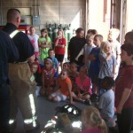 Lt Dwayne Rice show his fire fighting gear to the kids on a recent tour.